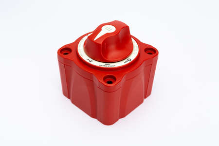 High angle view of a red on/off rotary switch, turned on, with white background