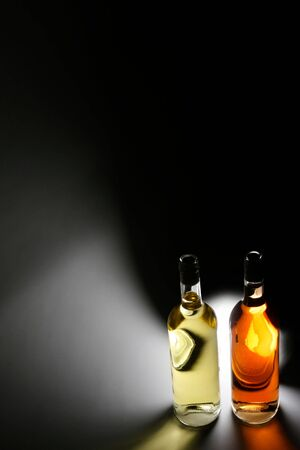Two bottles of wine, rose and white wine in front of a light source with lots of copy space photo
