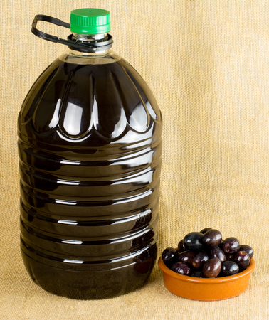 litre: 5 Litre Bottle of olive oil with olives in a small dish with copy space