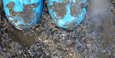 galoshes: child playing in a muddy puddle with blue wellie boots on .