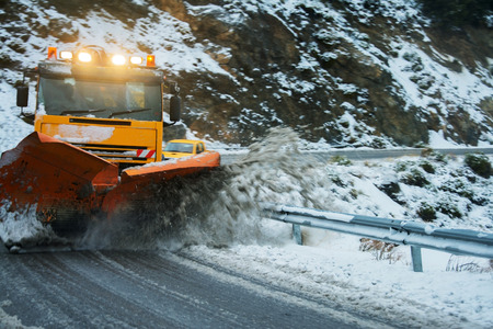 Snow plough moving snow on a dangerous bend after a snow storm. photo