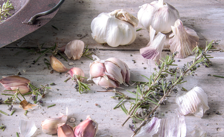 room for text: Garlic with Rosemary in an old rusty pot placed on a white farmhouse wooden table , with room for text