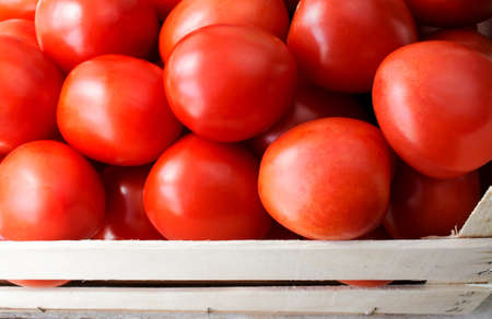 Close up shot of fresh tomatoes in a wooden crate photo
