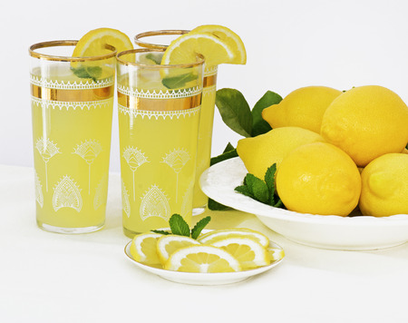 lemon: ice-cold drinks of  lemonade with mint in glasses with gold trim and a dish of freshly picked  lemons to the side with lemon leaves,  slice lemons at the front of the image,with shallow depth of field. room for text Stock Photo