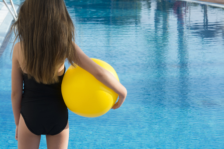 swimming costume: Young child with long brown hair, wearing a black swimming costume stood facing an empty pool, holding a yellow beach ball. room from text and copy space