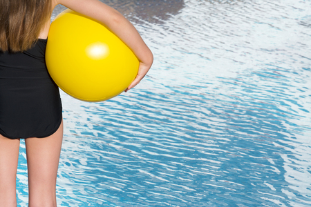 swimming costume: Partly showing a Young child with long brown hair, wearing a black swimming costume stood facing an empty pool, holding a yellow beach ball. room from text and copy space
