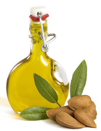 bitter: Fresh Organic Almond Oil in a glass swing top  bottle showing picked almonds and green leaves, often used for cooking, therapy, cosmetics, and well being. On a white background with room for copy space and text. Stock Photo