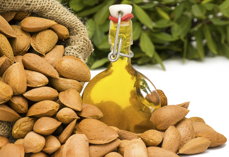 room for copy: Fresh Organic Almond Oil in a glass swing top  bottle showing picked almonds in a hessian sack with greenery in the blurred background,  often used for cooking, therapy, cosmetics, and well being.  Room for copy space and text.