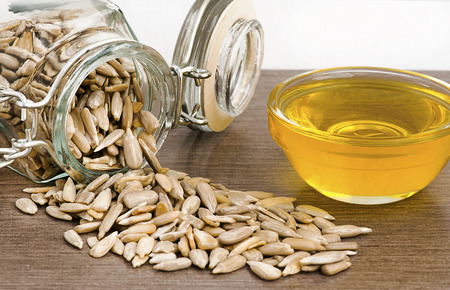 girasol: Pelados, las semillas de girasol de un frasco de conservas al lado de aceite de cocina de girasol en un plato de cristal. enfoque selectivo con un fondo blanco para el texto o el espacio de la copia