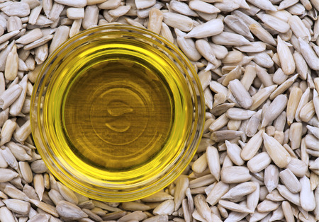 sunflower oil: Sunflower oil in a small glass dish, sat in a bed of sunflower seeds .