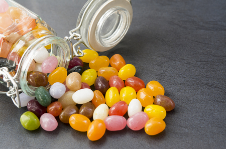 jellybean: Jellybean sweets coming from a mason jar on a dark worktop