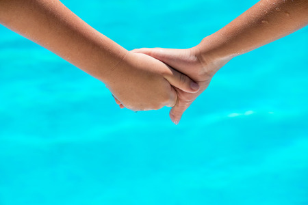 pool room: two happy young people holding hands in front of a clear blue swimming pool. room for text and copy space