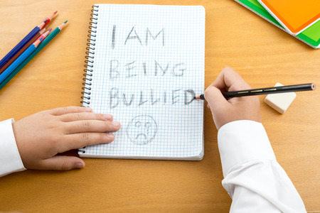 short phrase: An image  poster covering the Social Issues of child abuse,  schoolchild in uniform at a desk asking for help by a written message saying I am being bullied with a sad face . Room for copy space and text
