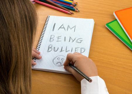 bullied: An Horizontal image  poster covering the Social Issues of child abuse,  schoolchild in uniform at a desk asking for help by a written message saying I am being bullied with a sad face . Room for copy space and text Stock Photo