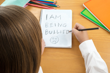 short phrase: An Horizontal image  poster covering the Social Issues of child abuse,  schoolchild in uniform at a desk asking for help by a written message saying I am being bullied with a sad face . Room for copy space and text Stock Photo