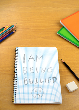 short phrase: An vertical image  poster covering the Social Issues of child abuse,  a note left on a desk by a child asking for help by a written message saying I am being bullied with a sad face . Room for copy space and text