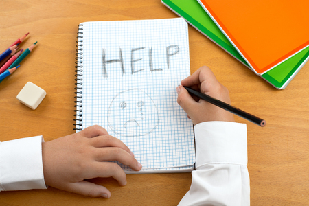 short phrase: An image poster covering the Social Issues of child abuse, schoolchild in uniform at a desk asking for help by a written message saying Help with a sad face . Room for copy space and text Stock Photo