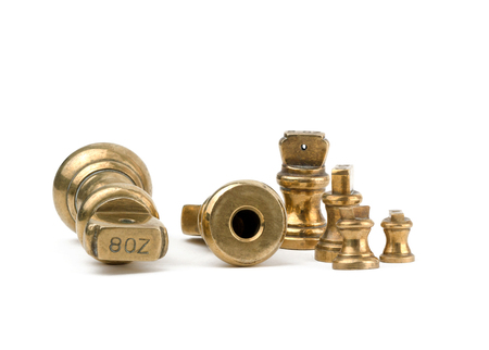 A set of antiques brass imperial weights  isolated on a white background. with the 8oz showing