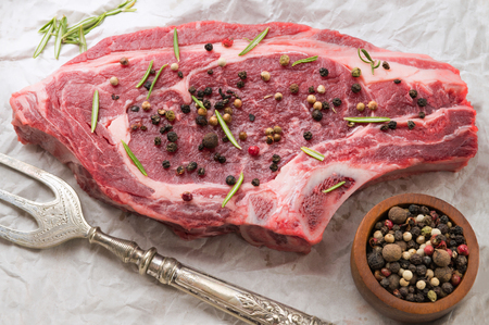raw organic beef seasoned with peppercorns and herbs on white paper with a large sliver fork,
