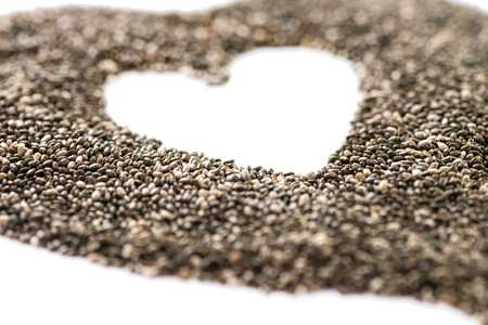 grained: macro shot of chia seeds shaped into a heart shot on a white background with copy space very shallow depth of field Stock Photo