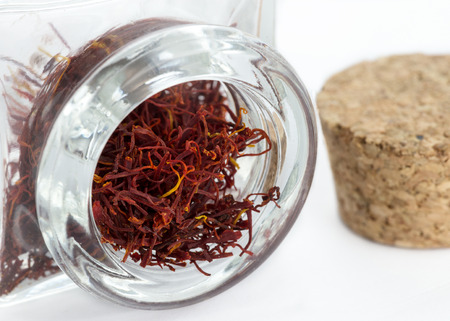close up image of Saffron in a thick glass jar with a cork stopper in the background, copy space to the right