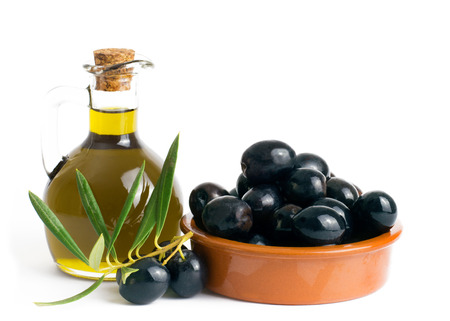 Olive oil with olives in a bowl on a white background with copy space