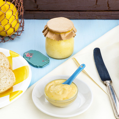 Square image of home made lemon curd with a glass jar showing blue yellow and cream colors  room at the top for copy space or text