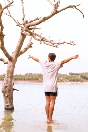 conceptual image of climate change. young man mimics the dying tree in a lake that has been flooded,filter added, blank sky in background for copy space