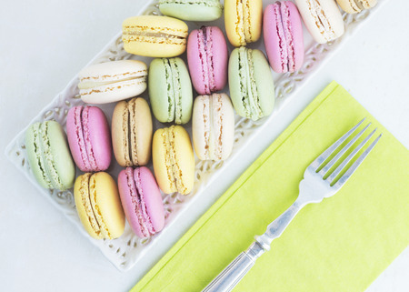 horizontal image of macaroons in  pretty summer colors with a lime green napkin and a silver fork ideal for text and copy space  such as a menu or notice.