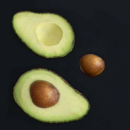 heathy: Square image of two halves of  avocado on a dark background the the seed removed and set to the side, copy space and room for text