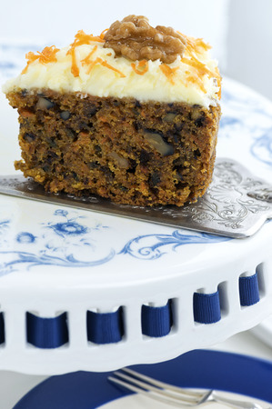 close up of moist carrot cake with walnuts, sat on a sliver cake slice and a blue and white cake stand, copy space at base of the image
