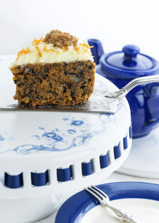 homemade carrot cake with walnuts on a pretty cake stand with sliver wear,  copy space in foreground and background image in blue and white colors. Stock Photo