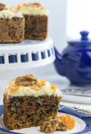 fragility: vertical image of a portion of cut carrot cake with nuts whole cake in the out of focus background. blue and white colors copy space at the top of the image