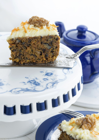 slice of moist carrot cake with walnuts on a blue and white cake stand with a sliver cake slice and fork, copy space in foreground and background Stock Photo