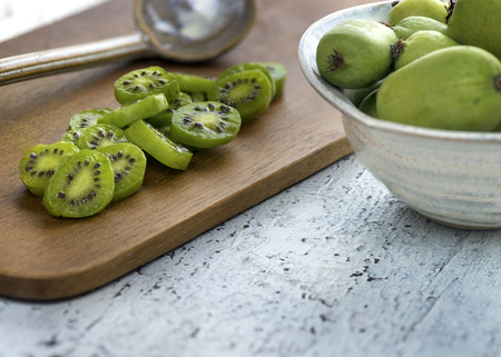 kiwi berries sliced and whole laid out on a wooden table selective focus with copy space Banco de Imagens