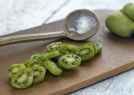 close up of kiwi berries slices on a wooden board selictive focus room for copy space Banco de Imagens - 85974321