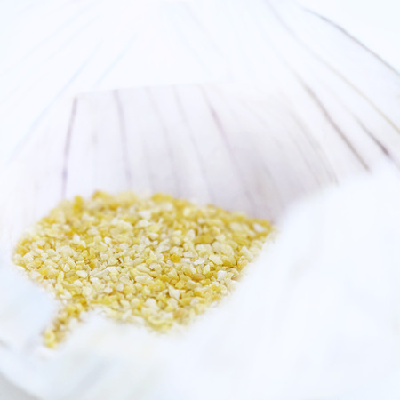atmosphere: extreme selective focus showing an square atmospheric close up of garlic granule salt light blurred background to aid copy space and text