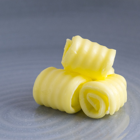 square image of fresh organic butter curled on a plate with space for text overlay and a blue blurred background