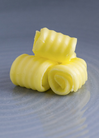 vertical image of fresh organic butter curled on a plate with space for text overlay and a blue blurred background