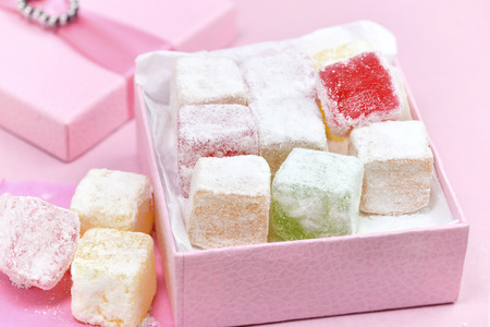 macro image of delicious colorful  sweet Turkish delight in a pretty box for valentines with a heart and pink background room for text and copy space