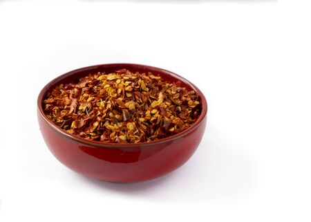 Hot chilli flakes and seeds in a red colored bowl isolated on a white background