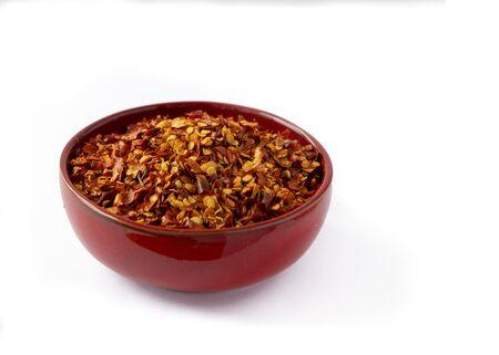 Scharfe Chiliflocken und Samen in einer roten Schüssel auf weißem Hintergrund