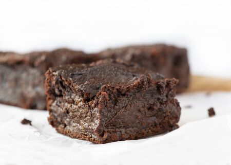 close up plant based vegan chocolate brownies made from sweet potatoes selective focus for copy space on a white background
