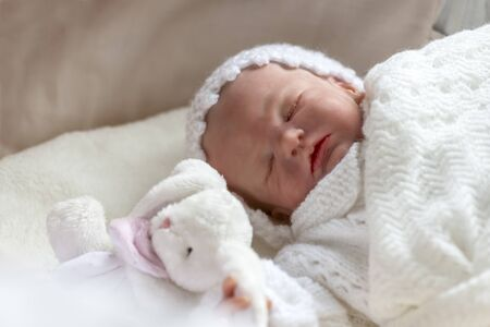reborn baby girl doll in a cot holding a small toy selective focus to ad copy space
