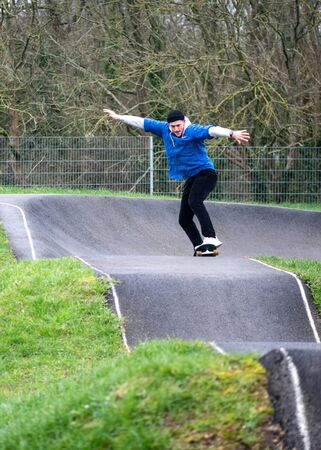 Young man in sportswear riding on skateboard with arms outstretched along hilly asphalt road performing tricks in skate park in daylight Фото со стока