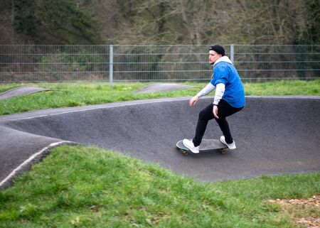 Side view of young focused man in warm sportswear and hat riding on skateboard along hilly asphalt path performing balance exercises in skate park