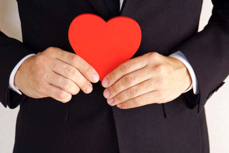 A businessman with a heart-shaped object.