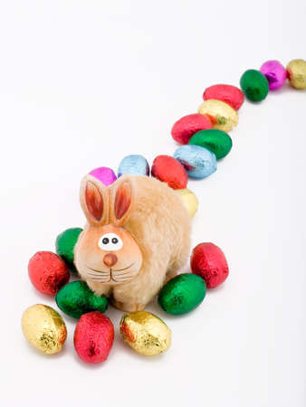 easter toy rabbit with some choclate eggs Stock Photo