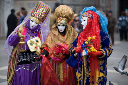 conceal: Three people are dressed for the Carnivale in Venice,Italy