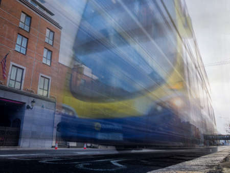 Close-Up Motion Blur Shot of a Blue and Yellow Double Decker Bus Driving Down the Street through a City - with Buildings in the Background Banco de Imagens